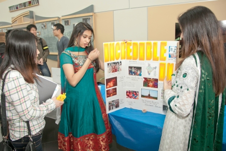 Student Ayesha Sharmeen (C) and Kaur Harleem (L) talk to a fellow student about  their display.
