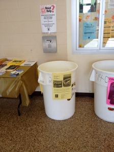 A food drive collection bucket is located on the second floor in the lobby of the College Community Center. By Rachel Robin, CCC Journalism Program