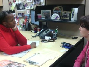 In this photograph Ms.Williams is shown with a former high school classmate Mary Bradley who is looking to find the right classes that she needs in order to graduate. On a typical day in her office Ms.Williams can advise up to twenty students.