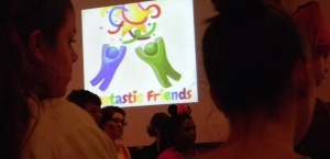 The Fantastic Friends Logo is displayed before the whole assembly of volunteers as they listen to Marissa Hacker, founder, as she explains what Fantastic Friends stands for.