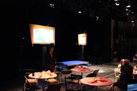 "The stage of the Dennis Flyer Theater transformed into a cafe/coffee house setting. The cast of ""Beats"" performed on and around the platform between the two ""TV"" projectors. By Will Hoheisel, CCC Journalism Program"