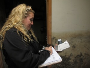 Marylee holds an air filtration system while checking info on her clipboard.  The tool she is holding is one of many used by Coastal Environmental Compliance when dealing with mold and other environmental hazards.