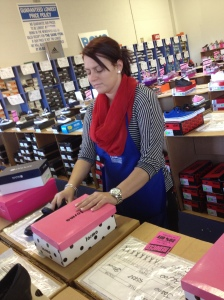 As customers begin to enter the store, employee Jessica fixes shoe boxes in the children's department. Most of her day will consist of fixing shoe boxes and straitening shoes.