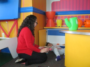 Sonia is in the RMHSNJ's playroom with Jaslene who suffers from Arthrogryposis Multiplex Congenita (AMC) which affects the joints and muscle tissues. Casts can be seen on Jaslene's legs from her treatments. Jaslene and her family are from California and have been coming to the RMHSNJ for several years while she visits a nearby hospital