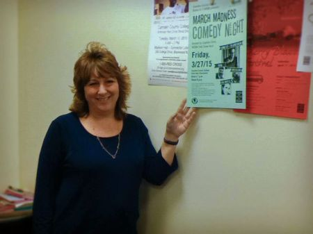 Jacqueline Tenuto, assistant dean for student development and support, stands with a comedy show poster. By Laura Wames, CCC Journalism Program