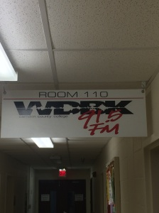 A 91.5 WDBK sign hangs in front of the radio station in the community center. Photo by Ryan Myers, CCC Journalism Program