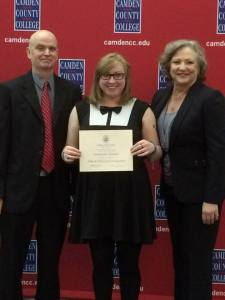 Samantha Hitman displays Film Excellence Award between two mentors and faculty members, Tom Murray and Allison Green
