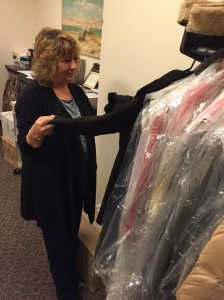 Assistant Dean for Student Development and Support Jacqueline Tenuto shows donated garments in her office. By Frank Rosa, CCC Journalism Program