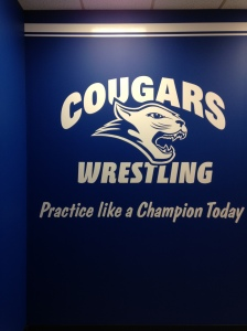 A sign hangs inside the Cougars wrestling locker room in the team's recently renovated building. By Laniesha David, CCC Journalism Program