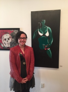 Noel Mercer stands with her work, Self Portrait: Shame. By Matthew Harris, CCC Journalism Program