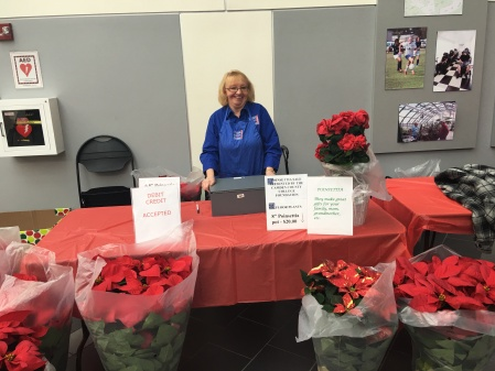 Myra Tryon, the Camden County College Foundation's secretary, sits at the holiday plant sale table. By Kenisha Prendegast, CCC Journalism Program
